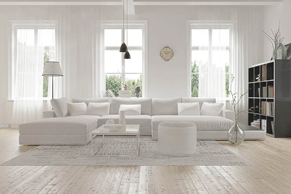 Modern spacious lounge or living room interior with monochromatic white furniture and decor below three tall bright windows with a dark bookcase accent in the corner. 3d Rendering